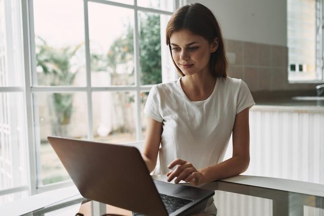 Junge frau mit einem laptop am tisch, der arbeitet und sich ausruht