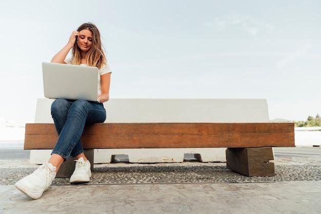 Junge frau mit einem laptop auf einer bank