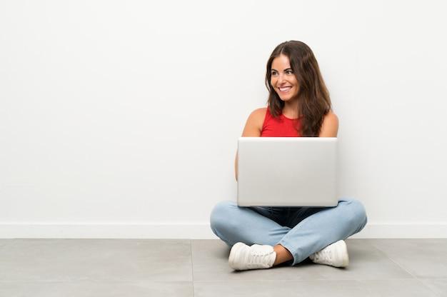 Junge frau mit einem laptop, der auf dem bodenlachen sitzt
