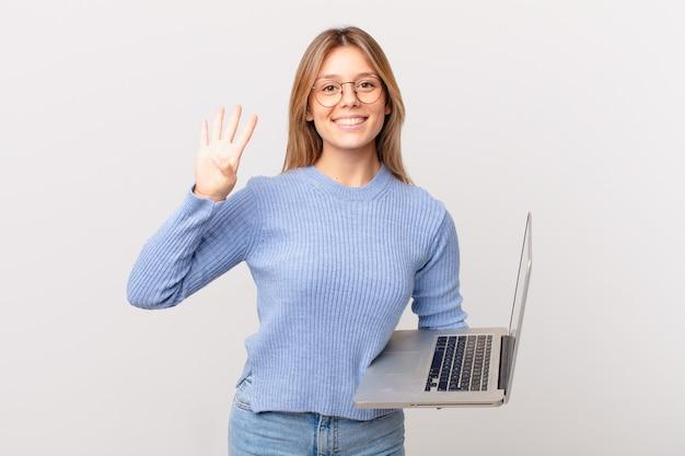 Junge frau mit einem laptop lächelt und sieht freundlich aus und zeigt nummer vier