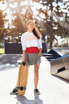 Junge frau mit einem longboard in ihren händen an einem sonnigen sommermorgen in einem skatepark