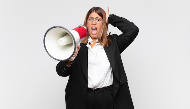 Junge frau mit einem megaphon, das sich gestresst, besorgt, ängstlich oder ängstlich fühlt, mit händen auf dem kopf, die bei einem fehler in panik geraten