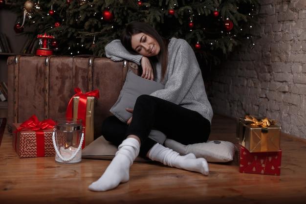 Junge frau mit einem niedlichen lächeln in einem gestrickten pullover in der schwarzen hose in den weißen socken sitzt auf dem boden nahe dem weihnachtsbaum im weihnachtszimmer unter den geschenken. mädchen denkt an die feiertage.