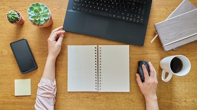 Junge frau mit einem offenen notizbuch unter verwendung eines laptop-computers auf einem hölzernen schreibtisch