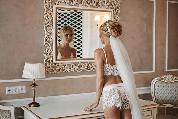Junge frau mit einem perfekten schlanken körper, in modischen spitzenwäsche und im schleier, im spiegel auf ihre reflexion auf vintage luxus interieur schauend