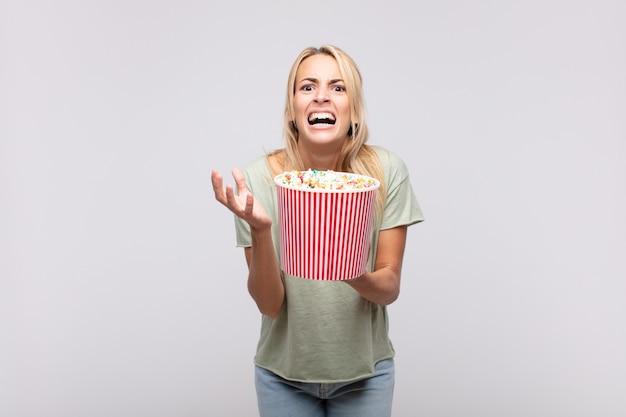 Junge frau mit einem popcorn-eimer, der verzweifelt und frustriert, gestresst, unglücklich und genervt aussieht, schreit und schreit