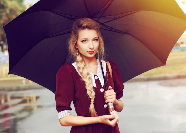 Junge frau mit einem regenschirm an einem regnerischen tag