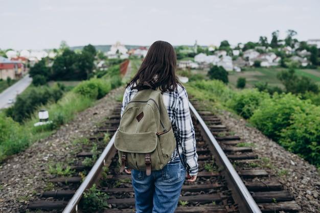 Junge frau mit einem rucksack auf einer eisenbahnstrecke.