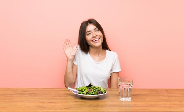 Junge frau mit einem salat, der mit der hand mit glücklichem ausdruck begrüßt