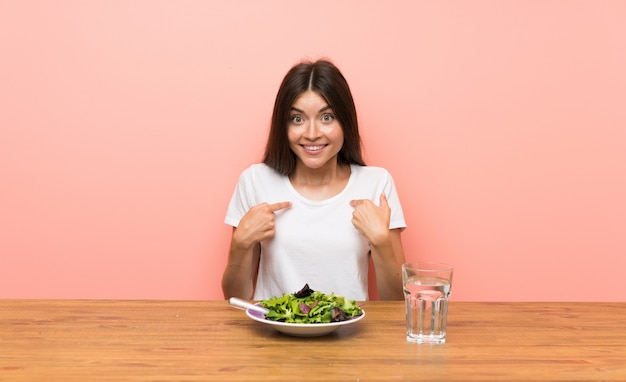 Junge frau mit einem salat mit überraschungsgesichtsausdruck