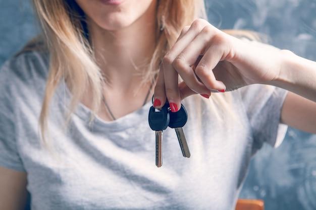 Junge frau mit einem schlüssel in der hand auf einem grauen