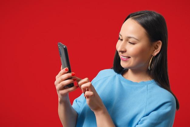 Junge frau mit einem smartphone auf rotem grund.