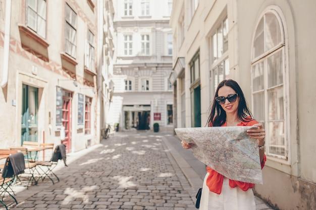 Junge frau mit einem stadtplan in der stadt. touristisches mädchen der reise mit karte in wien draußen während der feiertage in europa.