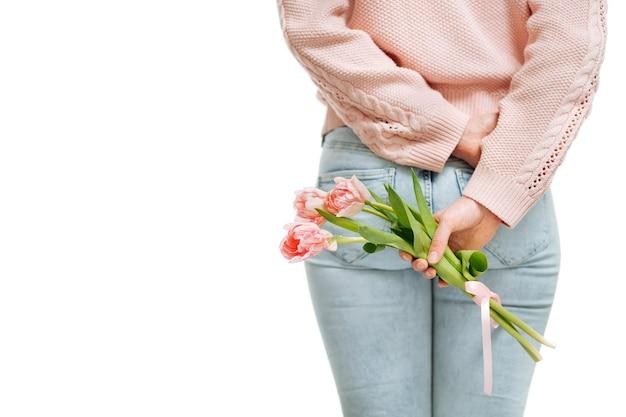 Junge frau mit einem strauß rosa tulpen hinter dem rücken auf weißem hintergrund. textraum, selektiver fokus.