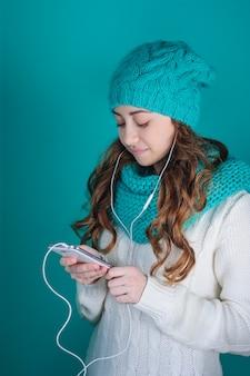 Junge frau mit einem telefon in seinen händen hörend musik auf kopfhörern
