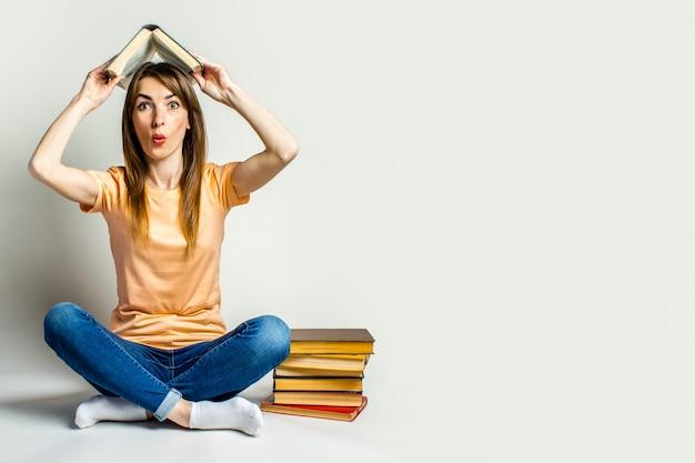 Junge frau mit einem überraschten gesicht hält ein buch über ihren kopf, während sie auf dem boden auf einem hellen raum sitzt. bildungskonzept. banner.