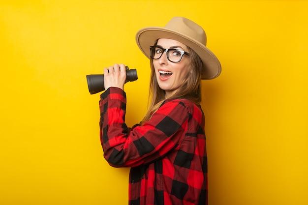 Junge frau mit einem überraschten gesicht in einem hut und einem karierten hemd, das fernglas in ihren händen auf einem gelben hintergrund hält.