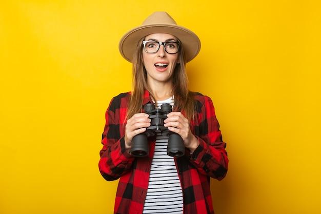 Junge frau mit einem überraschten gesicht in einem hut und einem karierten hemd, das fernglas in ihren händen auf einer gelben oberfläche hält