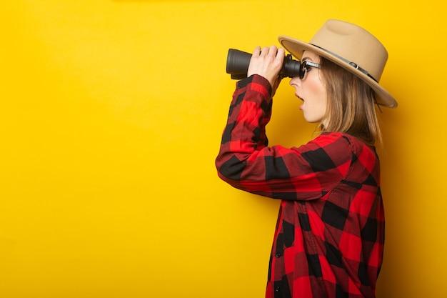 Junge frau mit einem überraschten gesicht in einem hut und einem karierten hemd schaut durch fernglas auf einer gelben oberfläche