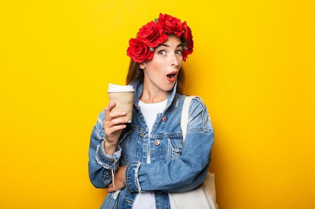 Junge frau mit einem überraschten gesicht in einer jeansjacke und einem kranz von roten blumen auf ihrem kopf, der eine pappbecher mit kaffee an einer gelben wand hält.