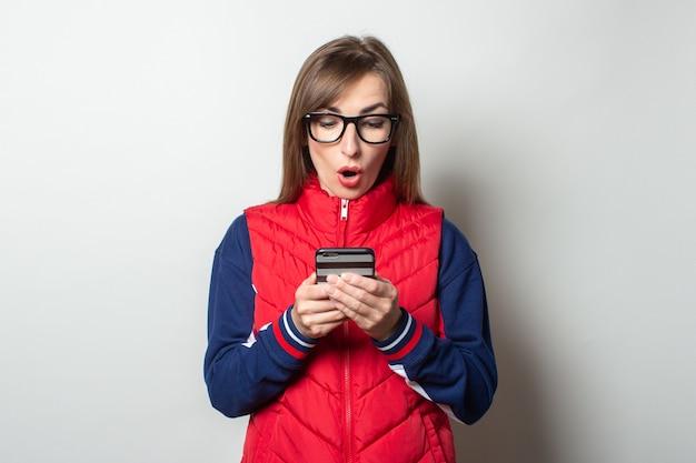 Junge frau mit einem überraschten gesicht in einer roten weste schaut ihr telefon gegen eine helle wand an