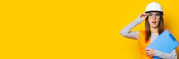 Junge frau mit einem überraschten gesicht in einer weste und einem schutzhelm hält ein klemmbrett auf einem gelben