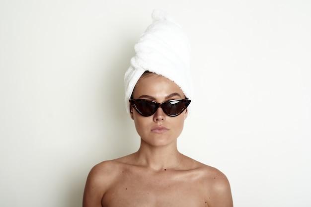 Junge frau mit einem weißen handtuch-turban auf dem kopf und in der sonnenbrille. ein wunderbares prätentiöses modell.
