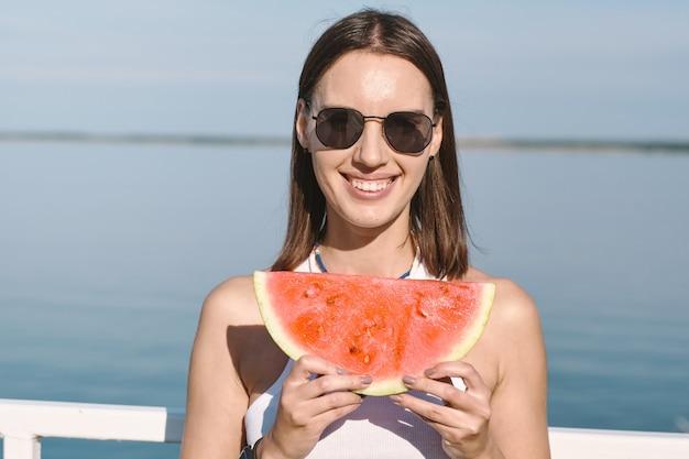 Junge frau mit einem zahnigen lächeln, das eine scheibe süße saftige wassermelone hält Premium Fotos