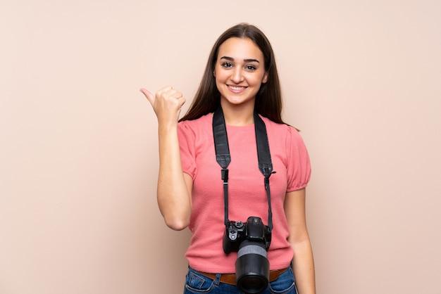 Junge frau mit einer berufskamera und zeigen auf die seite
