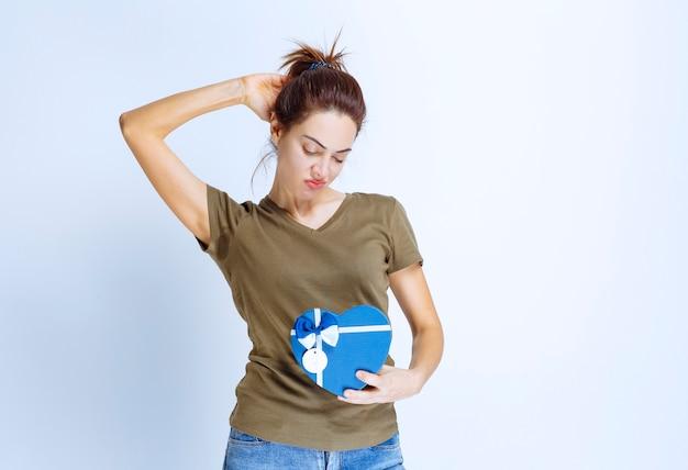 Junge frau mit einer blauen geschenkbox in herzform sieht unzufrieden aus
