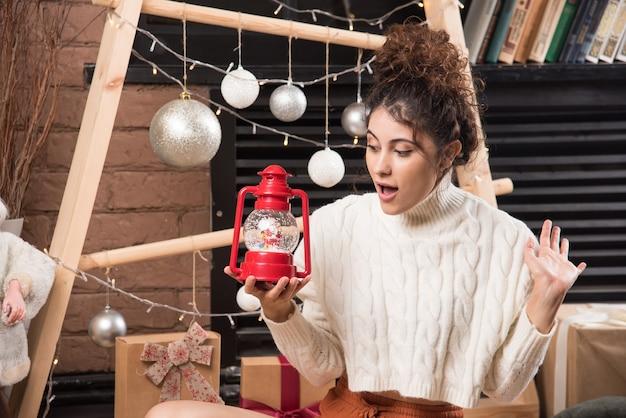 Junge frau mit einer roten weihnachtslampe