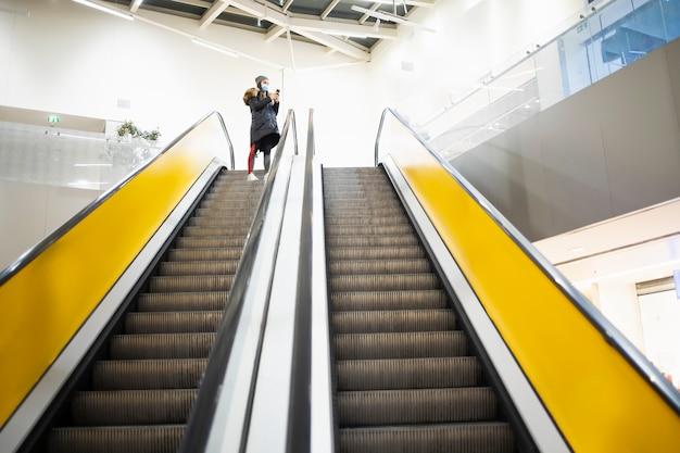 Junge frau mit einer schutzmaske, die die treppe auf einem flughafen nimmt