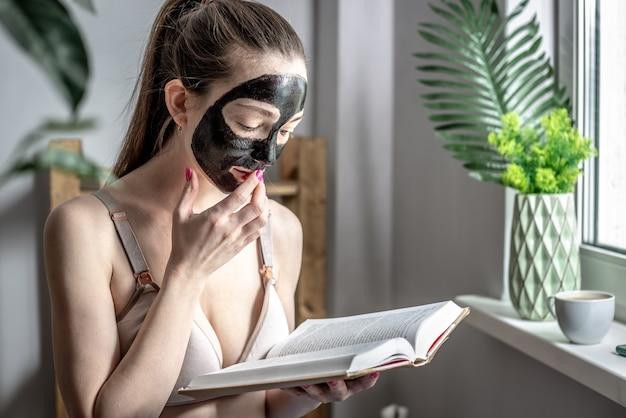 Junge frau mit einer schwarzen holzkohle-kosmetikmaske im gesicht liest ein buch