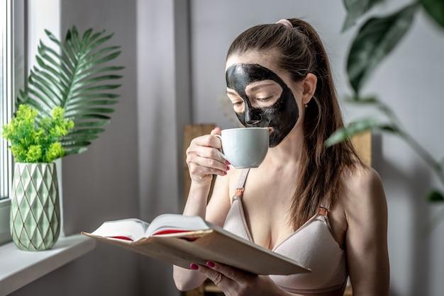 Junge frau mit einer schwarzen kosmetikmaske im gesicht und einer tasse kaffee liest ein buch