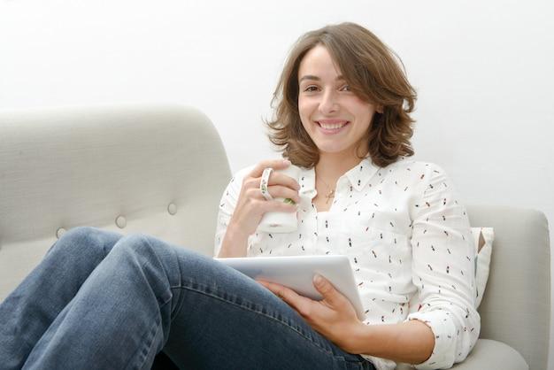 Junge frau mit einer tablette trinkt eine tasse tee