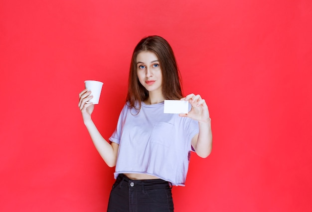 Junge frau mit einer tasse getränk, die ihre visitenkarte präsentiert.