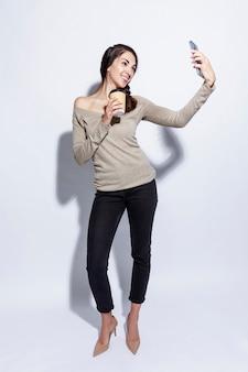 Junge frau mit einer tasse kaffee macht ein selfie am telefon. schöne schlanke brünette. vollständige höhe. weißer hintergrund. vertikal.