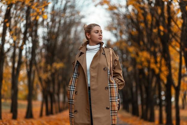 Modische junge frau in stilvoller herbstkleidung genießt