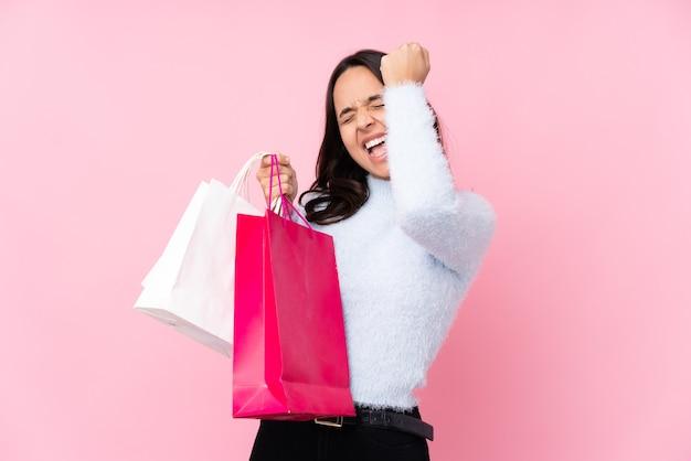 Junge frau mit einkaufstasche auf lokalisiertem rosa, das einen sieg feiert