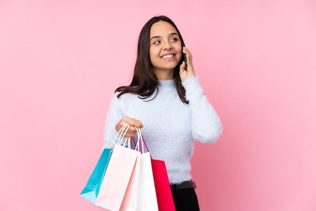 Junge frau mit einkaufstasche auf lokalisiertem rosa haltekaffee zum mitnehmen und einem handy