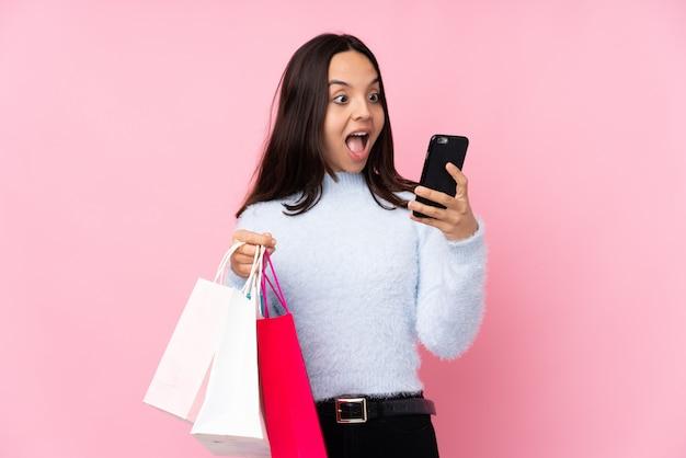Junge frau mit einkaufstasche über der lokalisierten rosa wand, die kaffee hält, um und ein mobile wegzunehmen