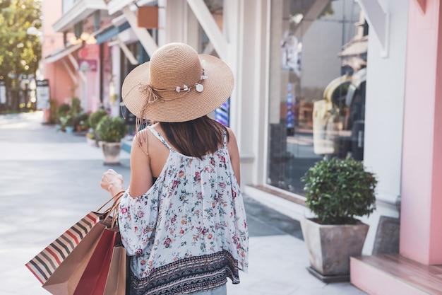 Junge frau mit einkaufstaschen am einkaufszentrum am schwarzen freitag, frauenlebensstilkonzept