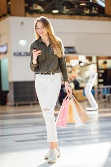Junge frau mit einkaufstaschen, die ihr smartphone für den kauf verwenden