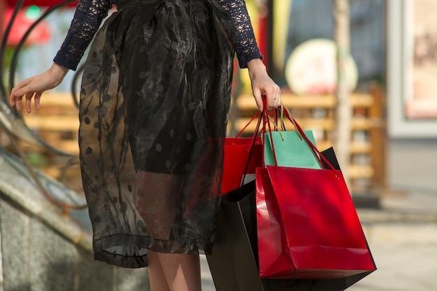 Junge frau mit einkaufstaschen, die in der stadt gehen