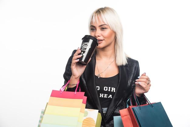 Junge frau mit einkaufstaschen, die tasse kaffee auf weißem hintergrund trinken. hochwertiges foto
