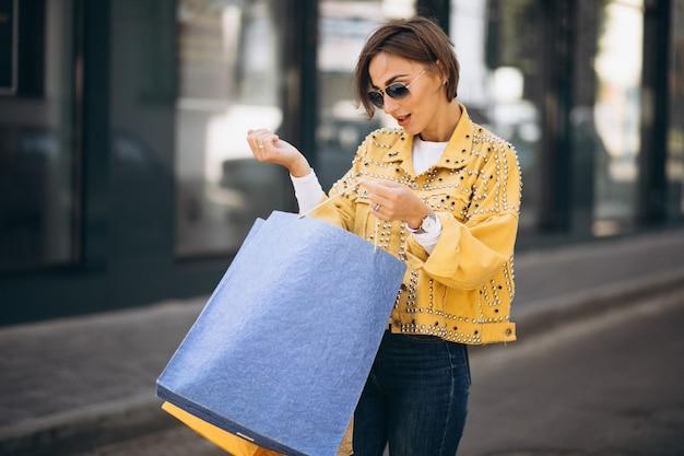 Junge frau mit einkaufstüten in der stadt