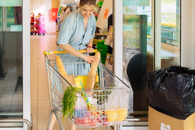 Junge frau mit einkaufswagen gefüllt mit lebensmitteln aus dem supermarkt am sommertag in freizeitkleidung mit purchacase