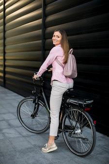 Junge frau mit elektrischem efahrrad der modernen stadt als sauberem stützbarem städtischem transport