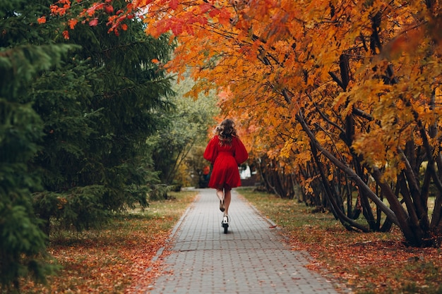 Junge frau mit elektroroller im roten kleid im herbststadtpark