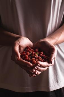 Junge frau mit erdbeeren in den händen